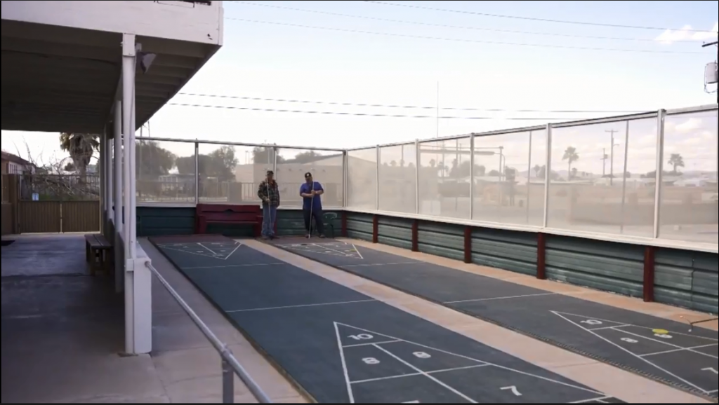 Two people playing shuffleboard on 1 of two shuffleboard lanes.