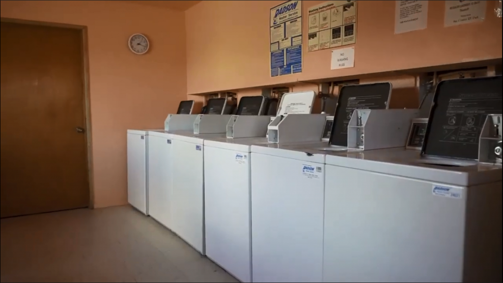 Six coin operated washing machines on one side of a laundry room.